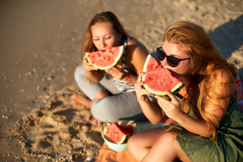 Freundinnen, die morgens frische Wassermelone an der Küste lachen und essen Zwei glückliche Freundinnen, die auf Tuch sitzen und stockfotografie