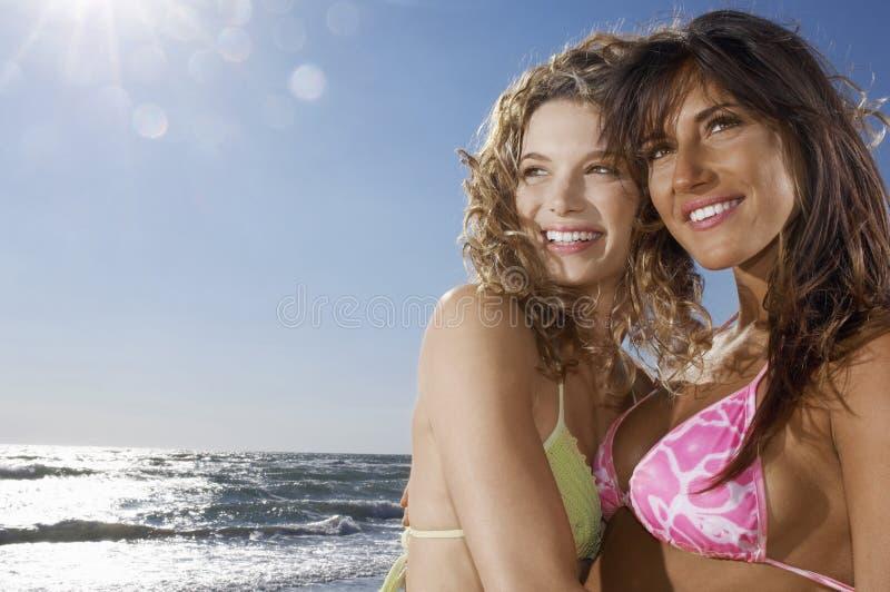 Freundinnen, die weg Strand betrachten lizenzfreie stockbilder