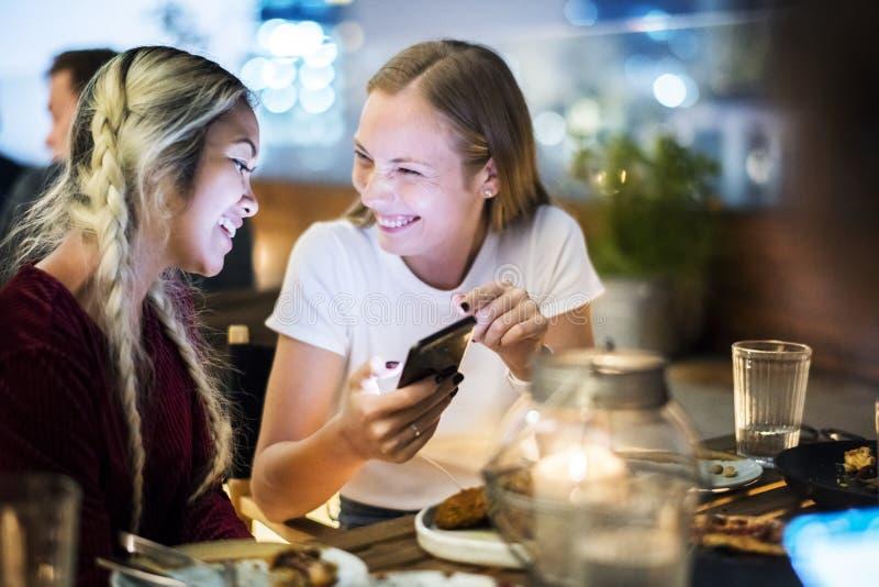 Freundinnen, die zusammen an einer Dachspitzenstange unter Verwendung eines s zu Abend essen stockfotos
