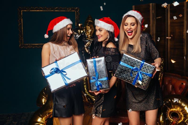 Freundinnen, die zusammen Weihnachtsgeschenke öffnen lizenzfreie stockfotos