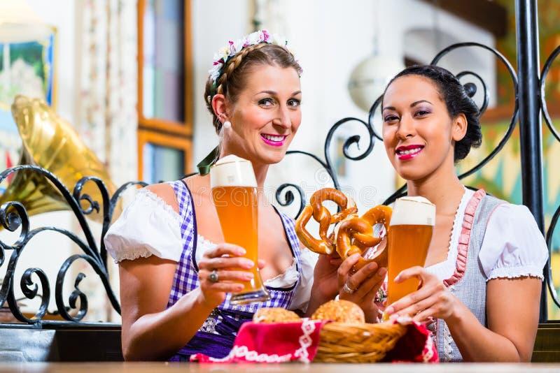 Freundinnen mit Brezel und Bier im bayerischen Gasthaus stockfoto