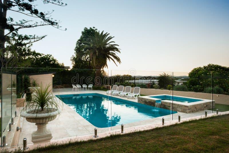 Freundlich verzierter Swimmingpool mit einem Garten und einem blühenden Topf lizenzfreie stockbilder
