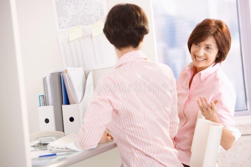 Freundliche Büroangestellte am Schreibtisch lizenzfreie stockfotos