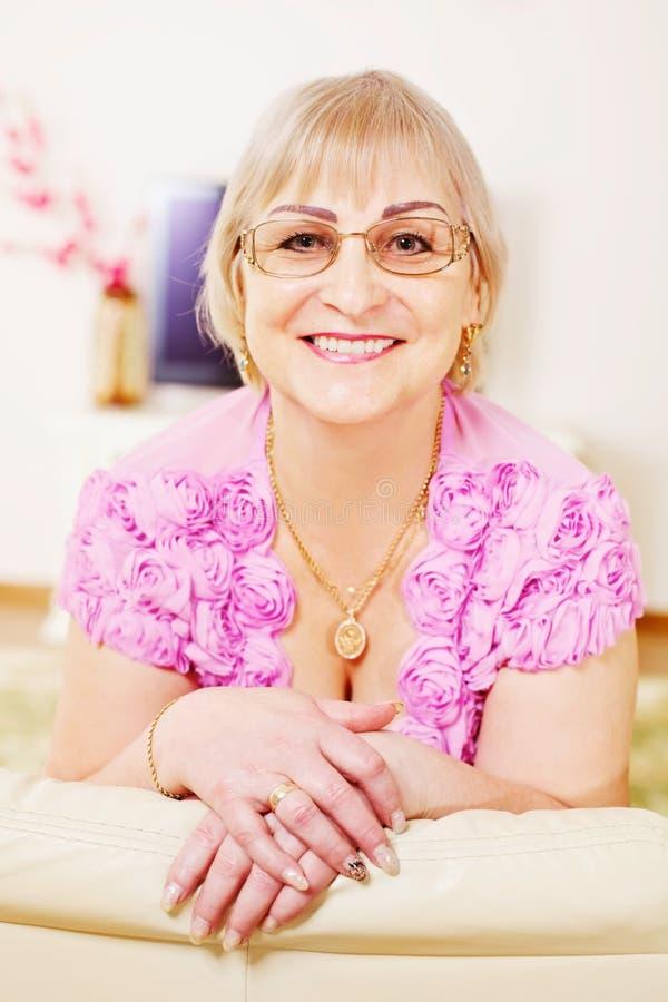 Freundliche fällige Frau auf Sofa lizenzfreie stockbilder