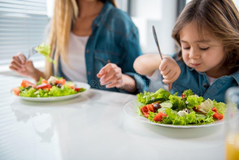 Freundliche Familie, die gesundes Lebensmittel schmeckt lizenzfreie stockbilder