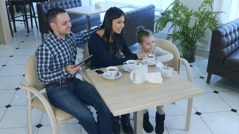 Freundliche Familie, die im Café, im Lächeln, in der Aufstellung und im Nachäffen sitzt lizenzfreie stockbilder