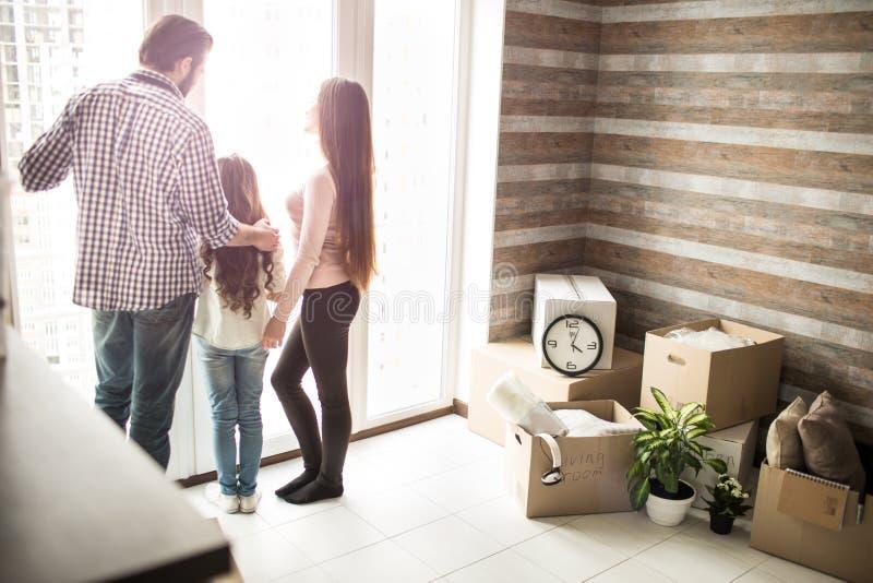 Freundliche Familie ist stehendes nahes Fenster und draußen schauen Es gibt Mannkästen auf der rechten Seite der Wohnung Leute lizenzfreie stockfotografie