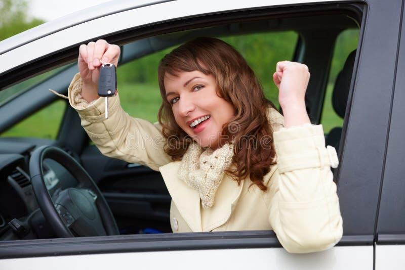 Freundliche Frau, die Autotasten zeigt lizenzfreie stockfotografie