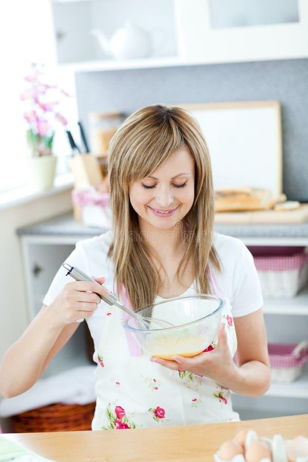 Freundliche Frau, die eine Mahlzeit in der Küche vorbereitet stockfoto