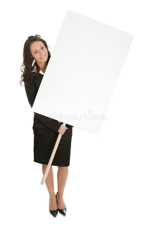 Freundliche Geschäftsfrauen, die leeren Vorstand darstellen lizenzfreies stockbild
