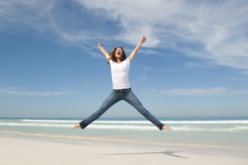 Freundliche glückliche junge Frau, die am Strand springt lizenzfreie stockfotos