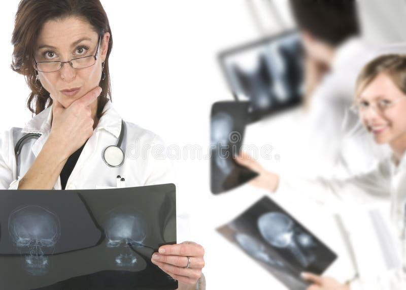 Freundliche junge Doktoren, die über einem weißen backgr lächeln lizenzfreie stockfotos