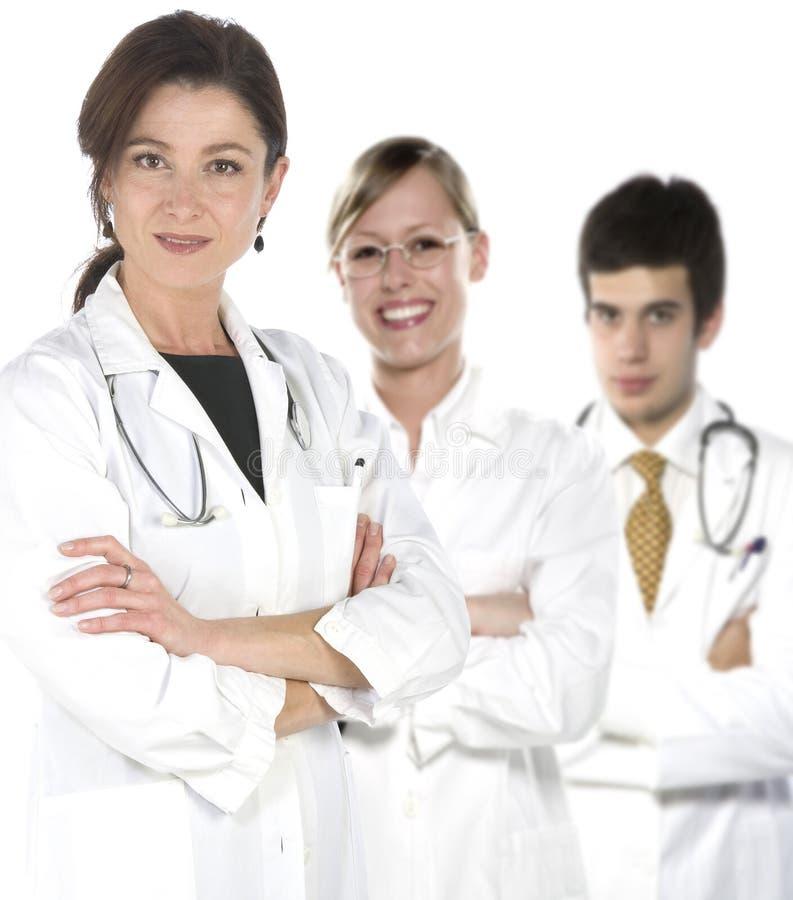 Freundliche junge Doktoren, die über einem weißen backgr lächeln lizenzfreie stockbilder