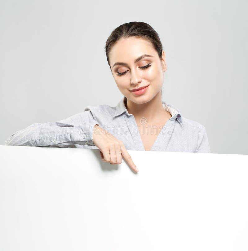 Freundliche junge Frau, die weißen leeren Schildpapierhintergrund zeigt und hält Glückliches Studentenmädchen, -geschäft und -aus stockfoto
