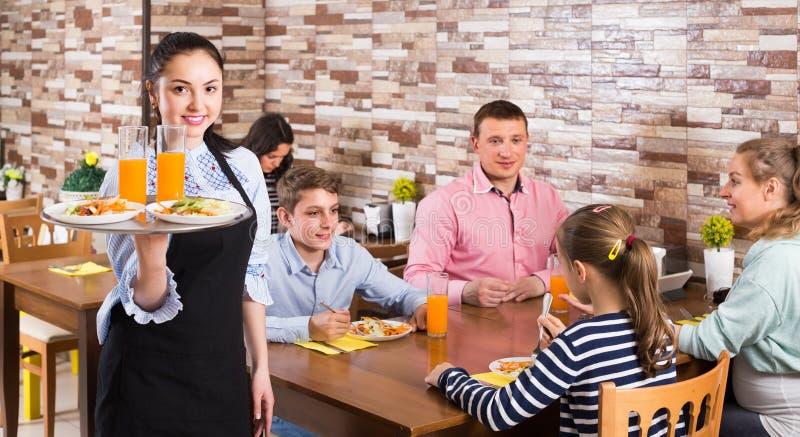 Freundliche junge Kellnerin begrüßt Sie zum Familiencafé stockfotografie