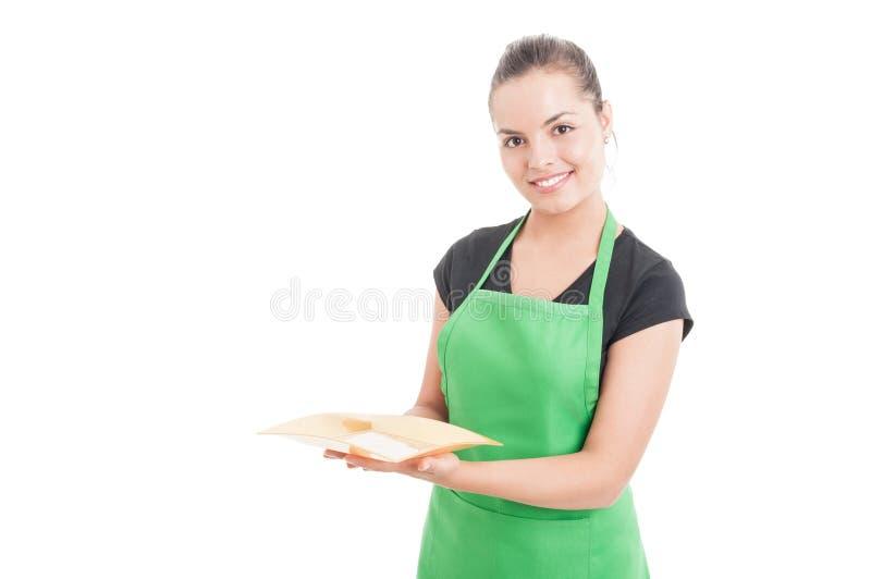 Freundliche junge Verkäuferinfrau, die leere Platte hält stockbilder