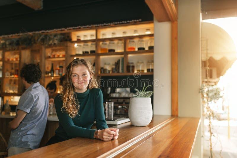 Freundliche Kellnerin, die auf dem Zähler einer modischen Stange sich lehnt lizenzfreie stockbilder