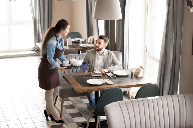 Freundliche Kellnerin, die dem Kunden Tee gibt lizenzfreies stockfoto