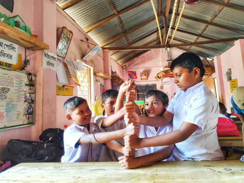 freundliche Kinder in der Schuluniform, die Spiele mit smily Gesichtern in einer lokalen Dorfgrundschule spielt stockfoto