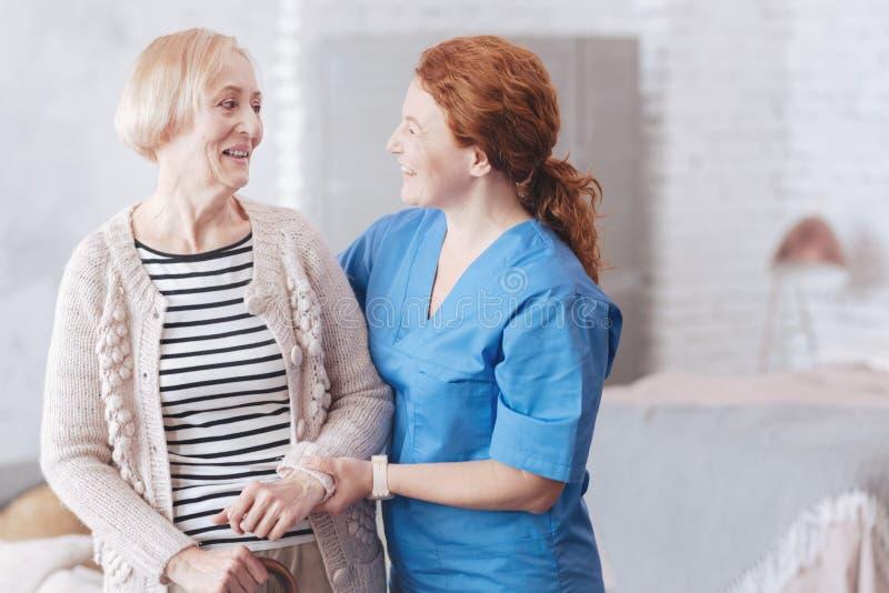 Freundliche Krankenschwester und weiblicher älterer Patient, die einander betrachtet lizenzfreies stockfoto