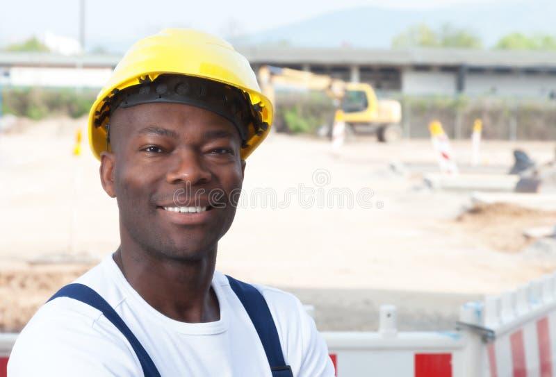 Freundliche lachende afrikanische Arbeitskraft an der Bauzone lizenzfreie stockfotografie