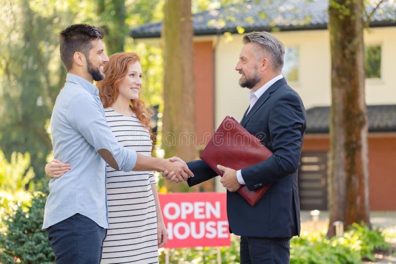 Freundliche Paare der Immobilienagentur lizenzfreie stockfotos
