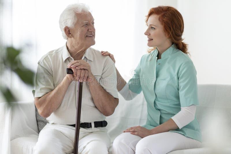 Freundliche Pflegekraft, die mit einem lächelnden älteren Mann mit walkin spricht lizenzfreies stockfoto