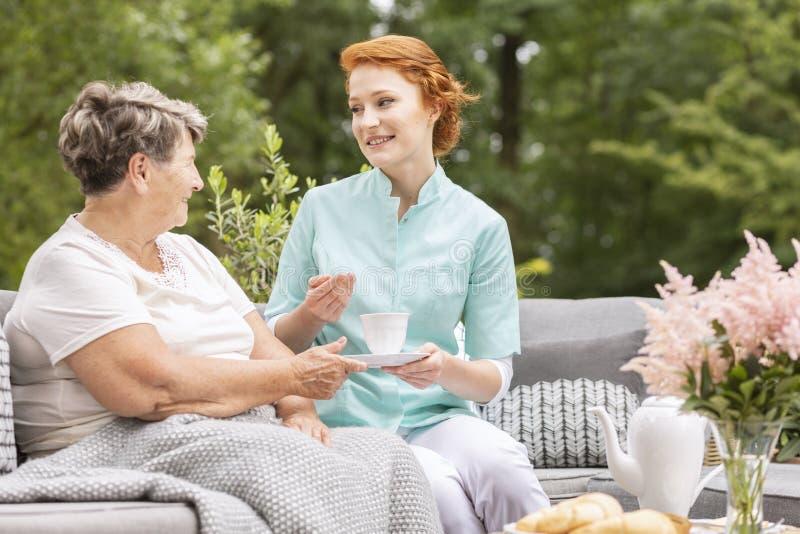 Freundliche Pflegekraft mit Tee sprechend mit einer älteren Frau im Kaimanfisch lizenzfreie stockbilder
