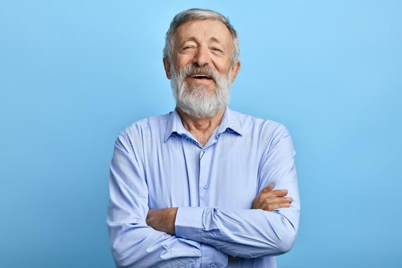 Freundliche Stellung des gut aussehenden Mannes mit den gekreuzten Armen, lachend über etwas lizenzfreies stockbild