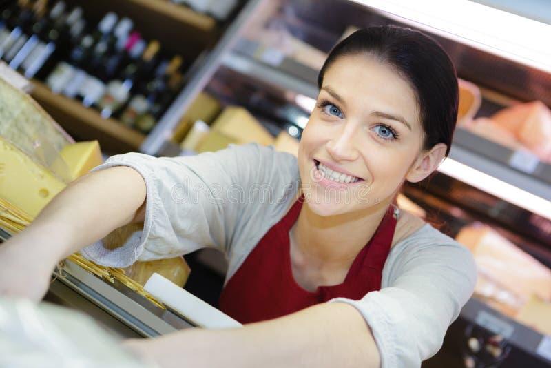 Freundliche Verkäuferin am Supermarkt lizenzfreies stockfoto