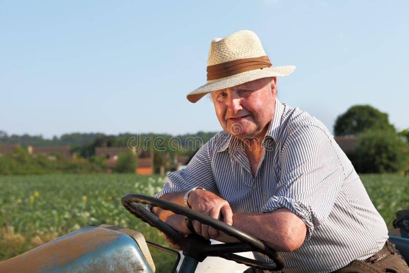 Freundlicher, älterer Gärtner auf seinem Traktor lizenzfreie stockfotografie