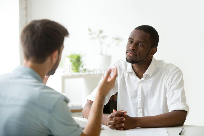 Freundlicher Afroamerikanerarbeitgeber, der auf Arbeitskandidaten d hört lizenzfreies stockfoto