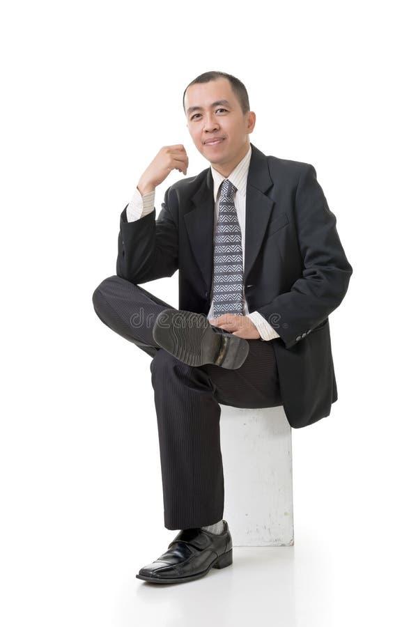 Freundlicher asiatischer Geschäftsmann sitzen lizenzfreie stockfotografie
