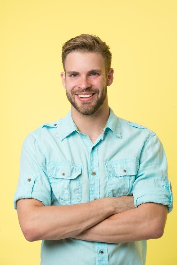 Freundlicher Berater Bemannen Sie das lächelnde Gesicht, das sicher mit gefaltetem gelbem Hintergrund der Arme aufwirft Mannshop- lizenzfreies stockfoto