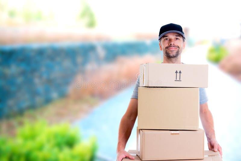 Freundlicher Briefträger mit Paketen stockfotos