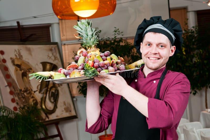 Freundlicher Chefkoch mit Früchten stockbild