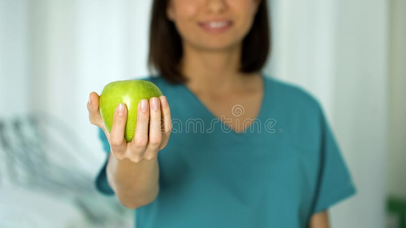 Freundlicher Damendoktor, der Apfelnahaufnahme, gesunde Nahrungsförderung, nährend hält lizenzfreies stockfoto