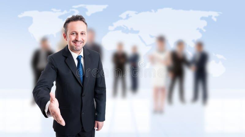 Freundlicher Geschäftsführer, der für Handerschütterung sich lehnt stockfotografie