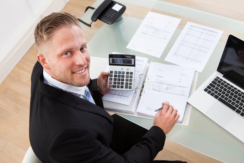 Freundlicher Geschäftsmann bei der Arbeit im Büro stockfoto