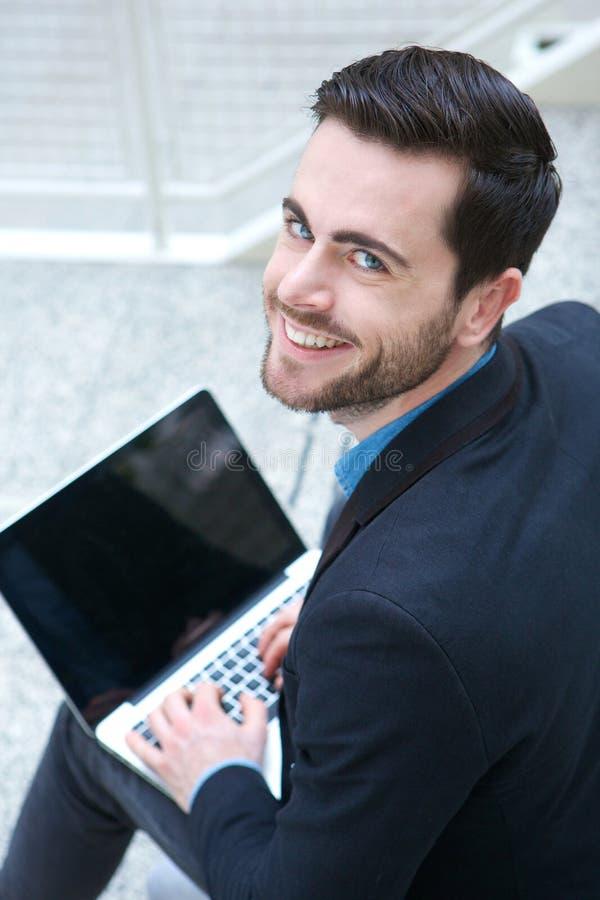 Freundlicher junger Mann, der an Laptop arbeitet stockfotografie