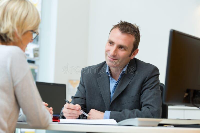 Freundlicher lächelnder Geschäftsmann und Geschäftsfrau im Büro lizenzfreie stockfotografie