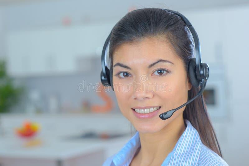 Freundlicher lächelnder Telefonbetreiber der jungen Frau am Arbeitsplatz stockbilder