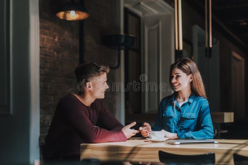 Freundlicher Mann und weibliche Kollegen besprechen Arbeit stockfotografie
