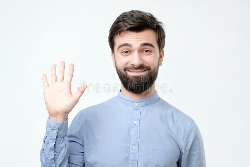 Freundlicher schauender höflicher junger hispanischer sagender Mann hallo stockfotografie