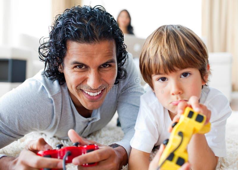 Freundlicher Vater und sein Sohn, die Videospiele spielt stockbild