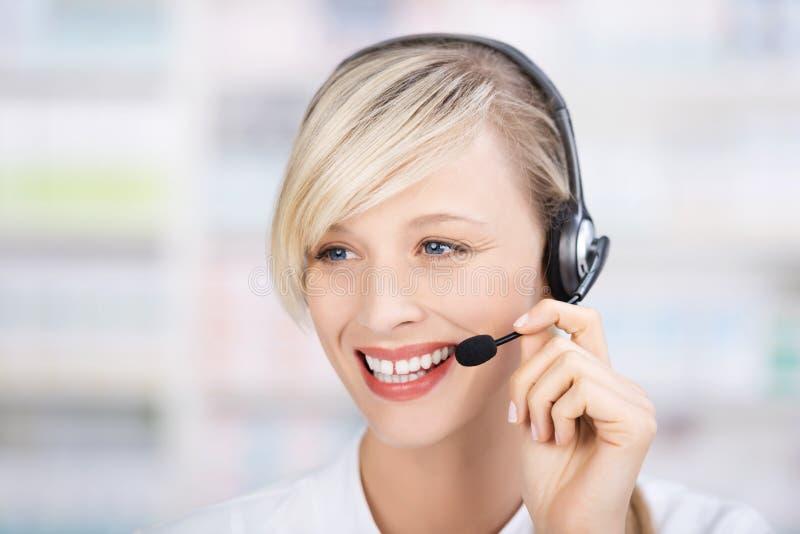 Freundlicher weiblicher Apotheker, der Kopfhörer verwendet lizenzfreie stockfotografie