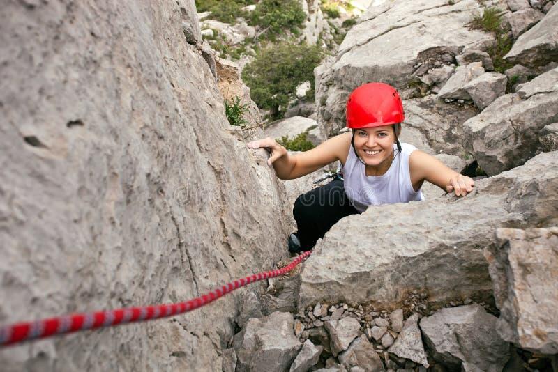 Freundlicher weiblicher steigender Bergsteiger ein Felsen stockfotografie
