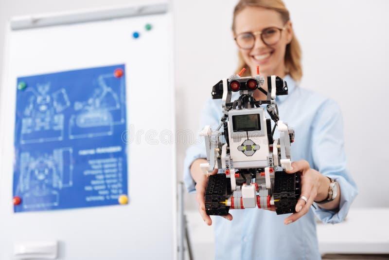 Freundlicher Wissenschaftler, der zuhause neuer Selbstautomatischen Roboter demonstriert lizenzfreie stockfotografie