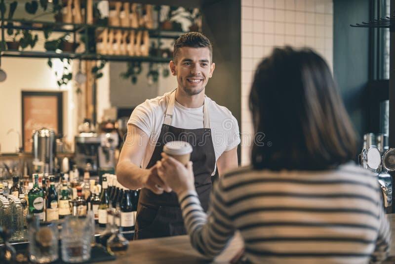 Freundliches barista, das dem Kunden Kaffee lächelt und gibt stockbild