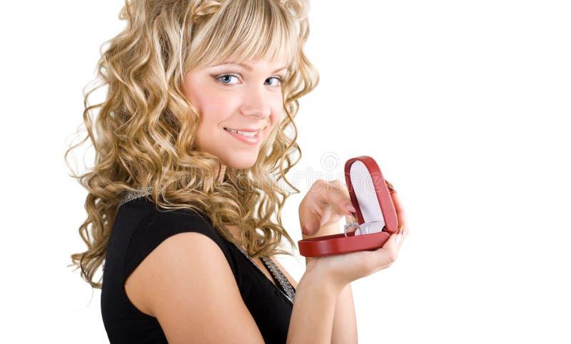 Freundliches blondes Mädchen, das einen Hochzeitsring anhält lizenzfreie stockbilder